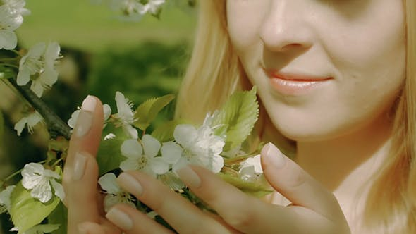Thumbnail for Cute Blonde Girl Touching Flowers In The Park