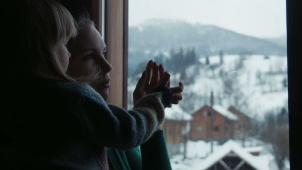 Thumbnail for Mother And The Daughter Look at Snowy Mountains