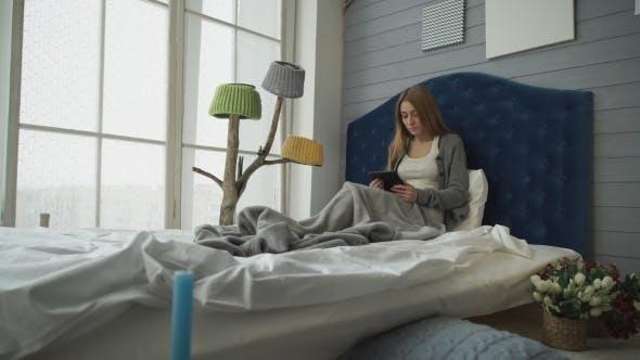 Thumbnail for junge frau sitzend auf ein bett mit ein tablette