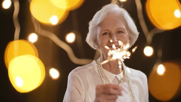 Thumbnail for Portrait of Happy Senior Woman with Sparkler