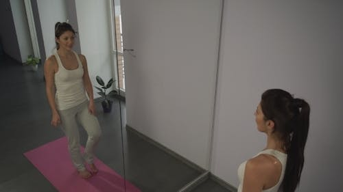 Young Woman Doing Yoga  Pose Tree In Front Of The Mirror