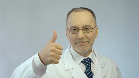 Thumbnail for Male Doctor Smiling at Camera, Making Thumbs-Up Hand Sign, Best Medical Aid