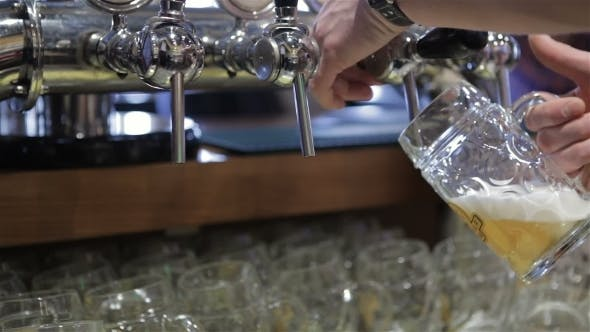 Of Barman Hand Pouring a Lager Beer
