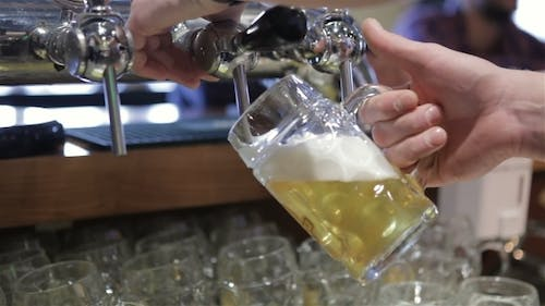 Bartender Pouring Draft Beer In The Bar