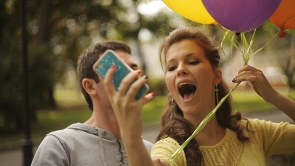 Cover Image for Young Couple Photographing Themselves With Balloons In The Park