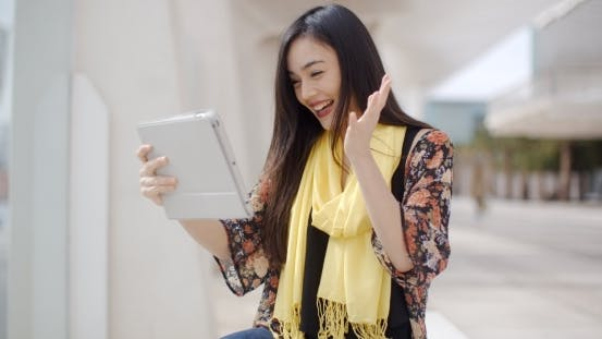 Thumbnail for Excited Woman Waving At Her Tablet Computer