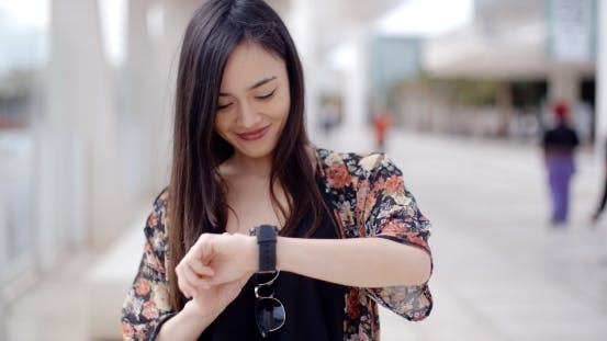 Thumbnail for Young Woman Looking At The Time With a Smile