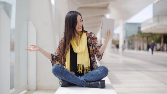 Thumbnail for Smiling Woman Waving At Her Tablet Computer