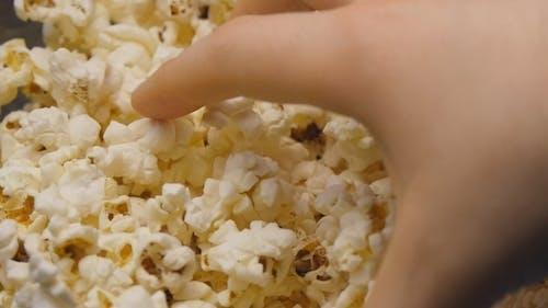 Hand ist Grabbing Popcorn