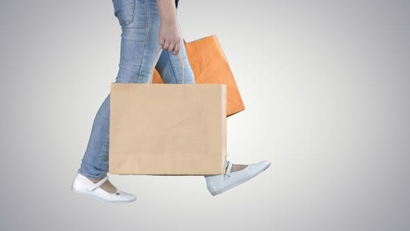 Cover Image for Cheerful school girl walking with shopping bags on gradient