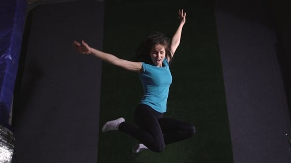 Thumbnail for A Young Woman in a T-shirt. Jumping on a Trampoline Is Ridiculous.