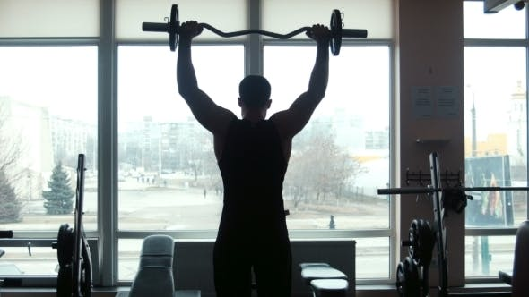 Thumbnail for The Man The Weightlifter Lifts a Barbell In a Gym