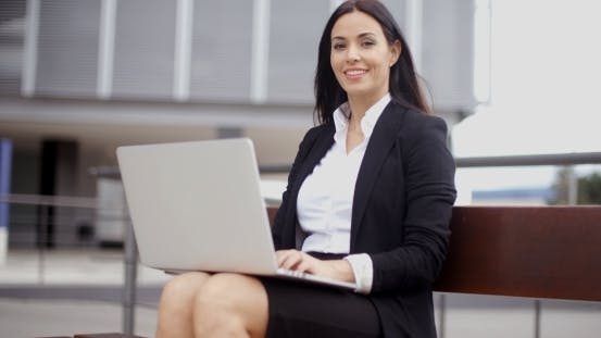 Thumbnail for Smiling Female Worker With Laptop On Bench