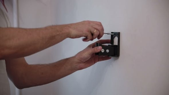 Thumbnail for Man Installs The Holder Bracket  On The Wall
