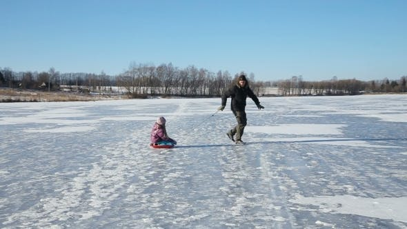 Thumbnail for Father And Daughter Sledding On Frozen Lake