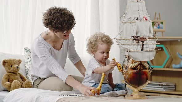 Thumbnail for Laughing Mother and Toddler Boy  Playing with Toys