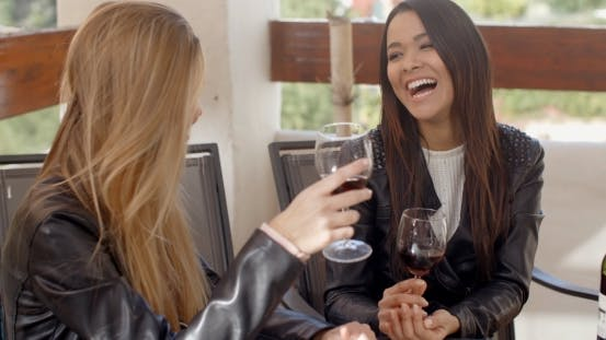 Thumbnail for Woman Laughing With Friend Over Wine