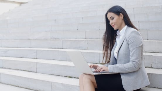 Thumbnail for Smiling Woman Using Laptop On Stairs