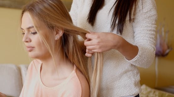 Thumbnail for Woman Looking Away While Friend Is Fixing Her Hair