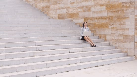 Thumbnail for Pretty Young Worker Sitting On Steps With Laptop