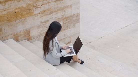 Thumbnail for High Angle View Of Woman On Laptop On Stairs