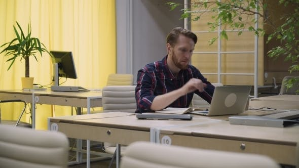 Thumbnail for Bearded Businessman Working At a Computer And  Drinking Coffee.
