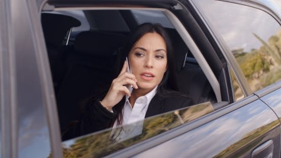 Thumbnail for Serious Female Executive On Phone In Limousine