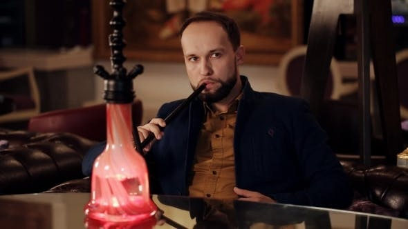 Man Smoking a Traditional Middle Eastern Hookah.