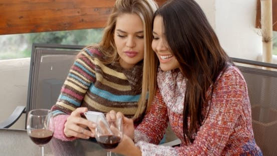 Cover Image for Girls At The Cafe Looking At Phone Together
