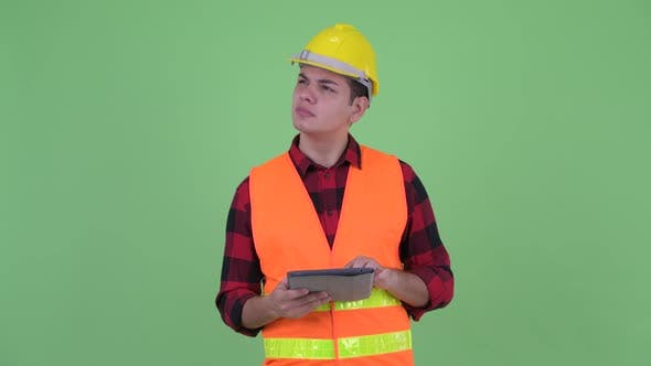 Thumbnail for Happy Young Multi Ethnic Man Construction Worker Thinking While Using Digital Tablet