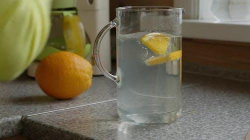 Junge kaukasische Mädchen bereitet Zitrus-Lemonade in der Küche vor.
