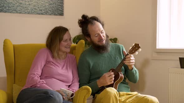Thumbnail for Man playing the ukulele to pregnant wife at the living room.