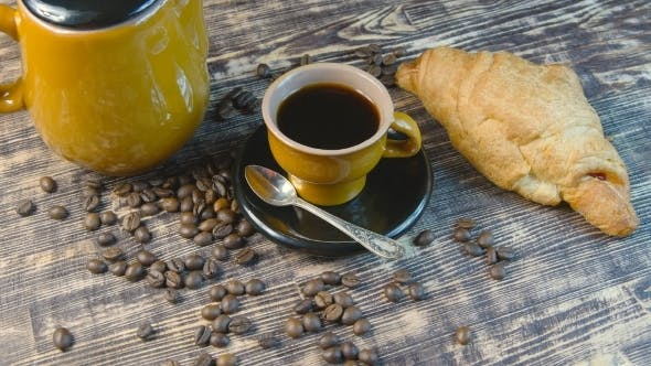 Cover Image for Coffee And Croissant Rotating On Wooden Table