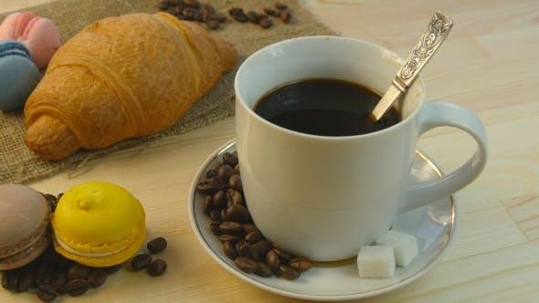 Thumbnail for Kaffee, Croissant und Makkaronen rotierend auf Holztisch