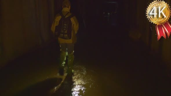 Backpacker in Gumboots is Walking by Water