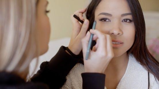 Serious Woman Getting Eye Liner Makeup