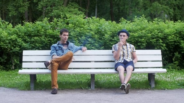 Thumbnail for Two Boys Sit In White Bench, Smoke Cigarette