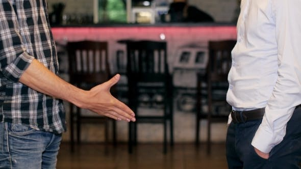 Thumbnail for Two Men In Jeans Stand Opposite Each Other And Give Man Handshake. Indoor