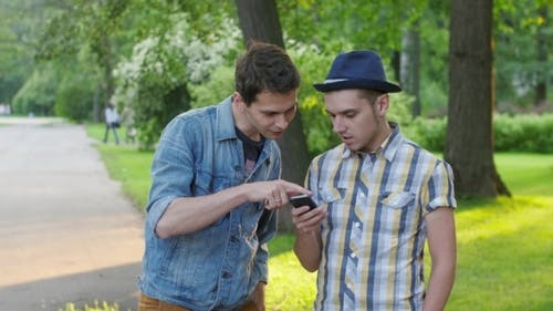 Boy Show Friend With Phone Something On Screen. Friend Look At Watch. Both Go