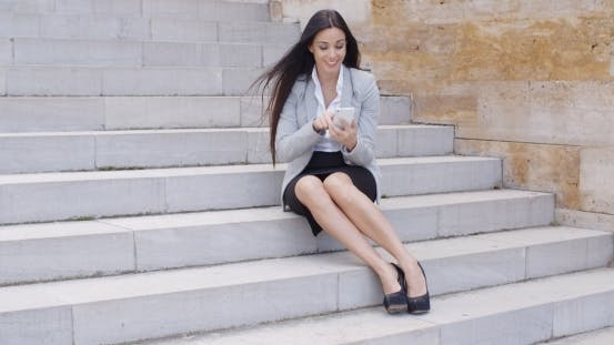 Thumbnail for Happy Executive With Phone And Seated On Stairs