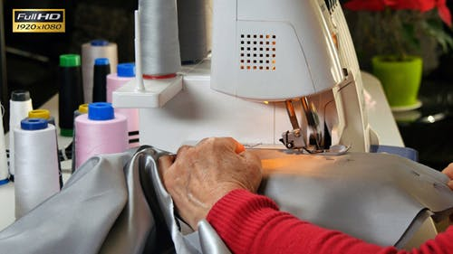 Seamstress Sews Clothes with her Over Lock Machine