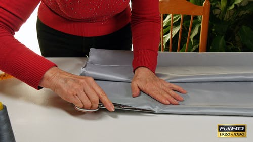 Dressmaker Cutting and Folding Clothes with Scissors