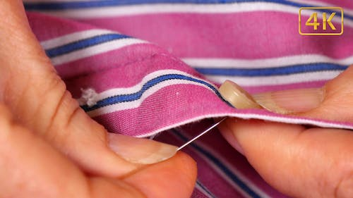 Seamstress Sewing a Button on a Shirt 4K