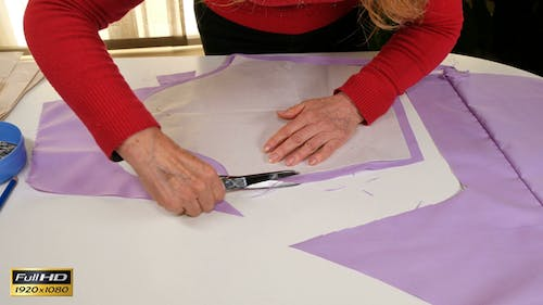 Seamstress Cutting Clothes Pattern