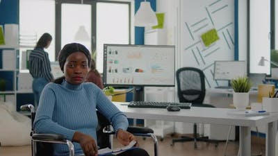Black Woman with Disabilities Looking at Camera Sitting in Business Office