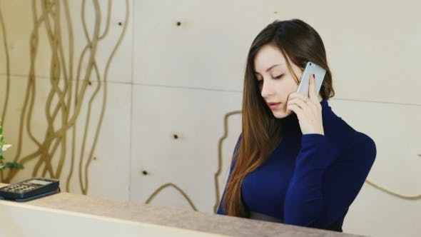 Thumbnail for Attractive Girl At The Reception Of The Hotel Or The Company, Talking On The Phone