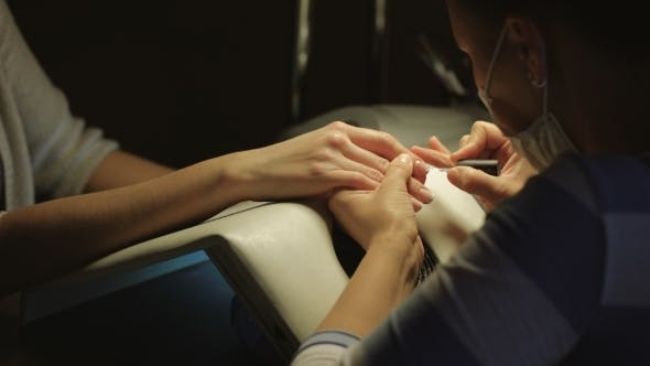 Cover Image for Woman In a Nail Salon Receiving Manicure By a Beautician. Beauty Treatment Concept.