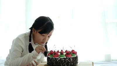Asian Girl Eating With Birthday Cake