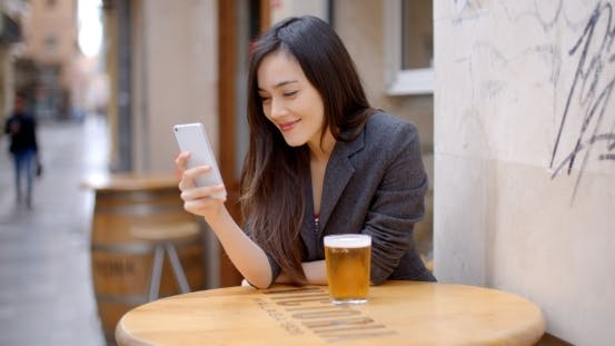 Thumbnail for Smiling Young Woman Relaxing With a Beer