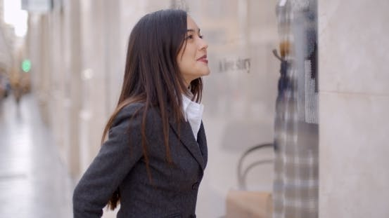 Thumbnail for Attractive Young Woman Window Shopping In Town
